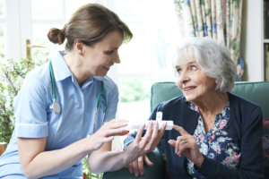 caregiver assisting patient to her medicines