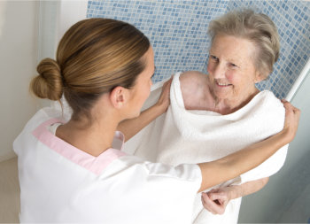 caregiver assisting her patient in chaning her clothes